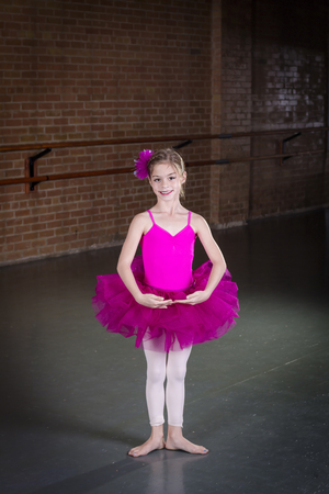 smile girl: Beautiful little dancer portrait at a dance studio. Vertical photo in a traditional dance studio. Lots of copy space above