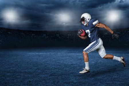 jugadores de futbol: Jugador de fútbol americano Correr para un touchdown en un gran estadio de fútbol profesional al aire libre en la noche