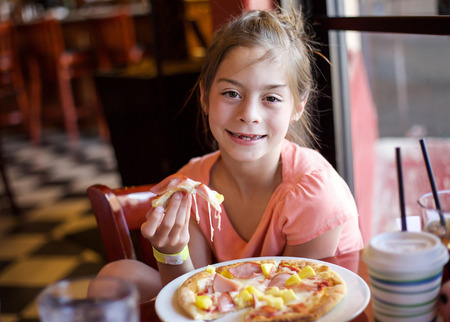 bacon portrait: Cute little girl eating a piece of pizza in a restaurant