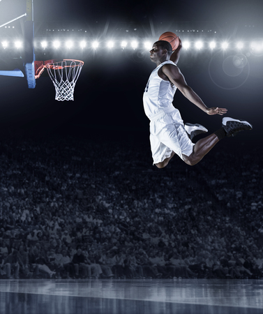 layup: Basketball Player scoring an athletic, amazing slam dunk in a professional basketball game Stock Photo