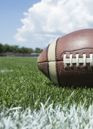 superbowl: Closeup photo of a football resting on an outdoor field