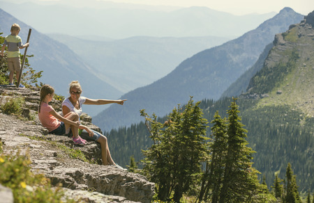 ledge: A family sitting together on a rocky ledge looking at a gorgeous view while visiting Glacier National Park in the Rocky Mountains Stock Photo