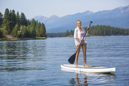Schöne Frau, Paddle-Boarding am malerischen Bergsee