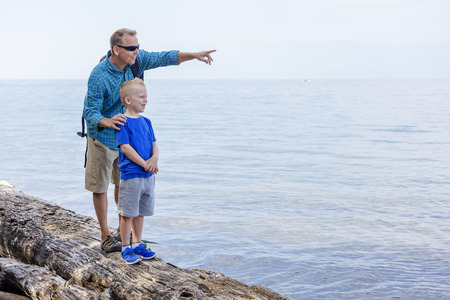 father and son: Father and son hiking together along a scenic lake. Lots of copy space and full length photo