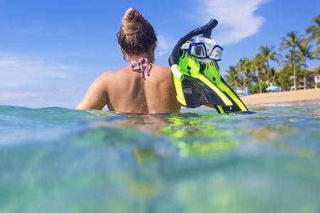 resort: Woman snorkeling in the ocean at a tropical island resort