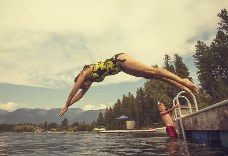 woman diving: Woman diving off the dock of lake while on summer vacation Stock Photo