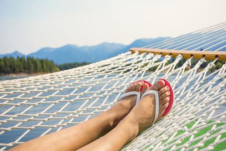 Mujer que se relaja en una hamaca en un hermoso lago de montaña