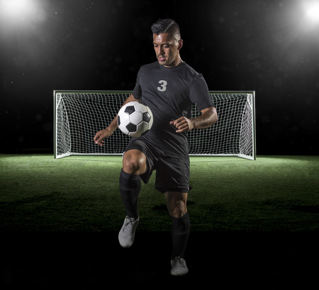 Soccer Player playing soccer on a dark background