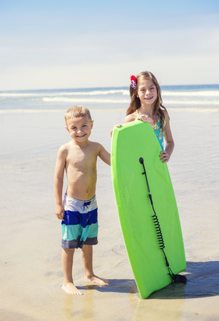 sea wave: Cute Kids playing together at the beach