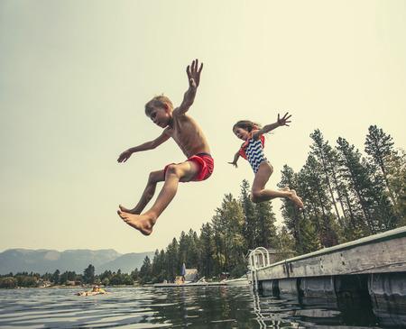 Niños saltando del muelle a un hermoso lago de montaña. Divirtiéndose en unas vacaciones de verano en el lago con amigos Foto de archivo