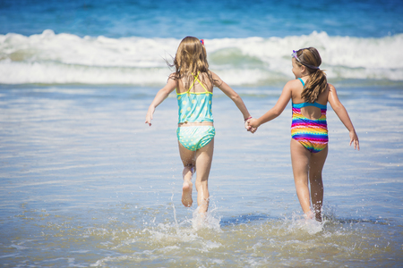 children swimsuit: Cute little girls playing at the beach together during summer vacation Stock Photo
