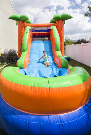 Smiling little girl playing on an inflatable slide bounce house outdoors