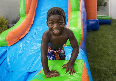brincolin: niño deslizándose por una casa inflables sonriendo Foto de archivo