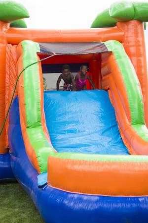 Happy smiling diverse children playing on an inflatable slide bounce house