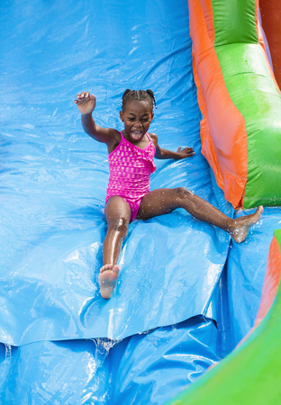 water activity: Smiling little girl playing on an inflatable slide bounce house outdoors