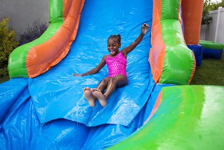 lazer: Menina feliz que desliza para baixo uma casa de salto infl
