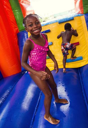 niños negros: niños sonrientes felices jugando en una casa inflables Foto de archivo