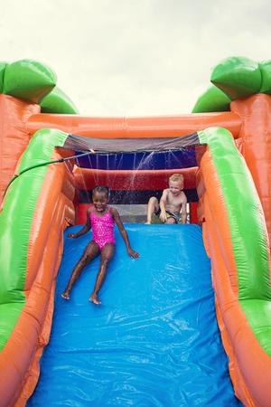 brincolin: niños sonrientes felices jugando en una casa de rebote tobogán inflable Foto de archivo