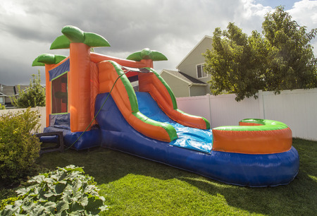 Inflatable bounce house water slide in the backyard Stock Photo