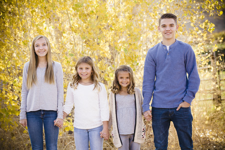 Portrait photo of Four cute kids holding hands together outdoors during an autumn day. Sibling group of three girls and boy of different ages