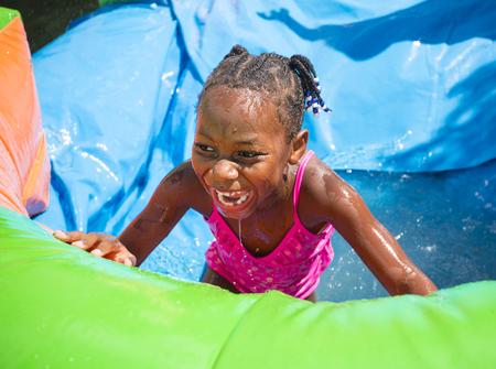 brincolin: niña que juega al aire libre en un tobogán de agua de la casa inflables sonriendo Foto de archivo
