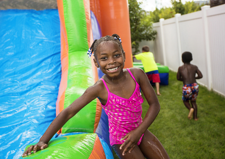 bounce: Smiling little girl playing outdoors on an inflatable bounce house Stock Photo