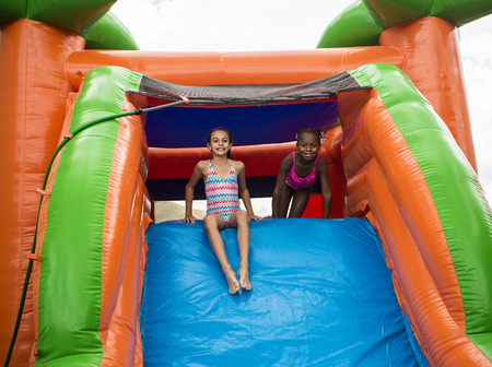 Happy little girls sliding down an inflatable bounce house Stock Photo