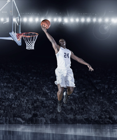 layup: Athletic African American Basketball Player scoring a layup basket during a professional basketball game in a crowded arena Stock Photo