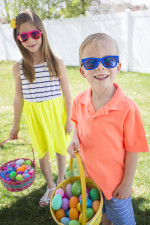 Cute kids on an easter egg hunt outdoors collecting eggs during a family celebration