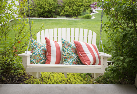 Beautiful wooden front porch swing with comfortable pillows
