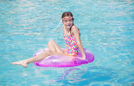 float tube: Beautiful young girl playing in the pool in summer time. Lots of copy space and water