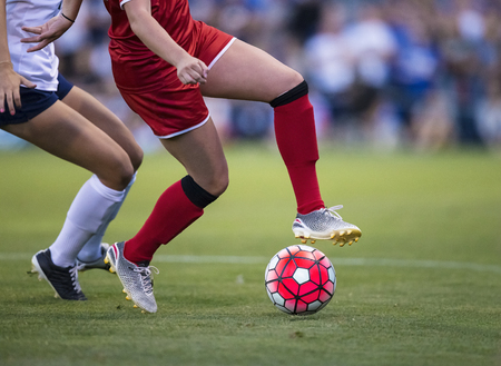 women playing in a soccer game on a soccer field