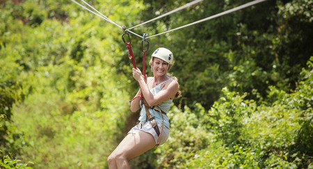 adventurer: Smiling woman riding a zip line in a lush tropical forest Stock Photo