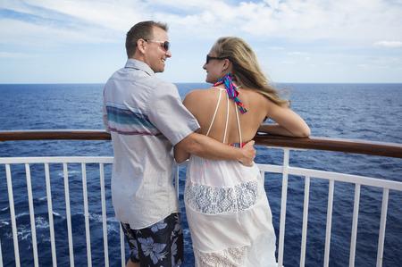 Gelukkig echtpaar lachend op het balkon van hun cruiseschip terwijl hij op vakantie samen