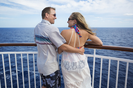 Happy married couple smiling on the balcony of their cruise ship while on vacation together Stock Photo