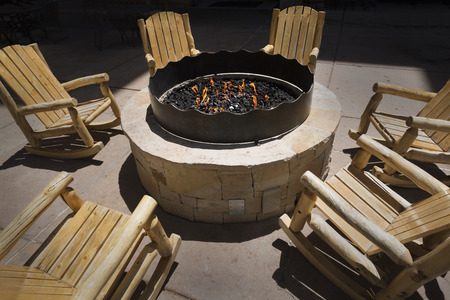 fire pit: Large outdoor fire pit surrounded by wooden rocking chairs