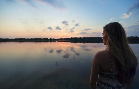 mujer mirando el horizonte: Mujer que disfruta del aire libre que miran una hermosa puesta de sol Foto de archivo