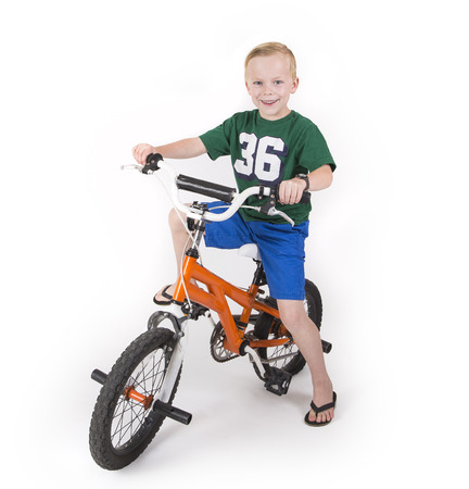 boy kid: Cute boy riding his bike isolated on white background Stock Photo