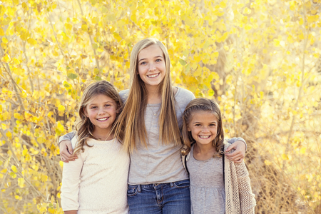 Beautiful Portrait of smiling happy kids outdoors. Three sisters standing together for a cute picture on a warm fall day Stock Photo