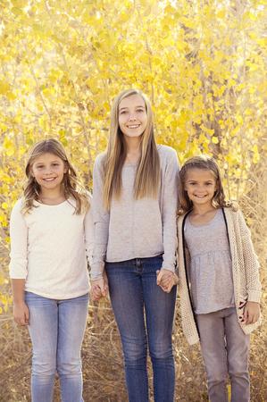 Beautiful Portrait of three cute little girls outdoors photo