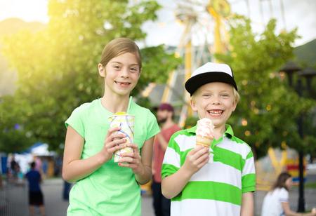 Kinderen eten ijs en traktaties op het carnaval. Weinig jongen en meisje die hun snoepje houden behandelen en een vrolijke glimlach tonen. Leuke zomerse activiteit Stockfoto