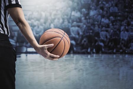 árbitro de baloncesto sosteniendo una pelota de baloncesto en un juego en un estadio lleno de gente. Sosteniendo la pelota en su mano durante un tiempo muerto. Enfoque selectivo en la pelota. Los aficionados y la multitud y la cancha de baloncesto Foto de archivo