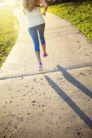 Blonde vrouw die langs een stadspad op een zonnige avond loopt. Gezicht op haar benen van achteren als ze loopt. Zonneschijn en felle zon
