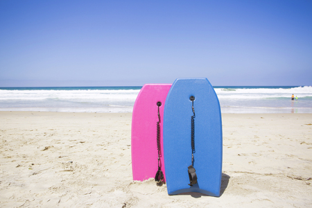 Two colorful boogie boards resting on a pristine beach. Ready to ride and have fun in the ocean on a clear summer day. Vacation time Stock Photo