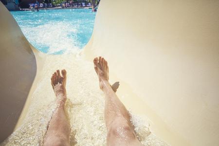 Standpunt foto van een man die tijdens een warme zomerdag een waterglijbaan in een openlucht waterpark brengt. Veel exemplaarruimte. Focus op de voeten en waterglijbaan Stockfoto