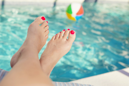 Beautiful sexy female feet relaxing by the swimming pool. Great pedicure photo. Stock Photo