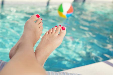 Mooie sexy vrouwelijke voeten ontspannen bij het zwembad. Grote pedicure foto.