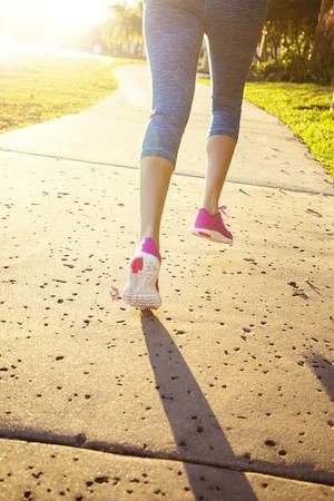 Vrouw joggen in een uitzicht op het stadspark van achteren. Vrouw die langs een stadspad op een zonnige avond loopt. Gezien haar benen van achteren als ze loopt. Zonneschijn en felle zon