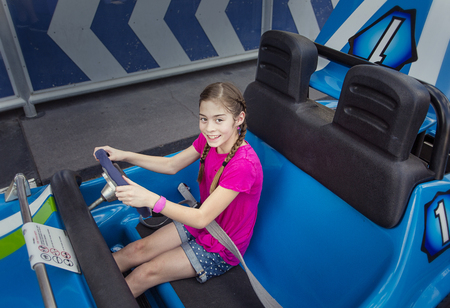 Kind geniet van een dag in het pretpark. Zitten in een autobus pretpark rit klaar om te gaan op een warme zomerdag buitenshuis. Glimlachend en plezierig en klaar om te gaan rijden