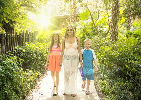 Mooie jonge familie die buiten een tropisch resort samen op een leuke jungle eiland familie vakantie loopt.